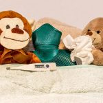 Two sick teddy bears with tissues, hot bottle, and thermometer.