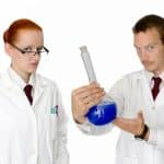 Two scientists hold a test tube with blue liquid.